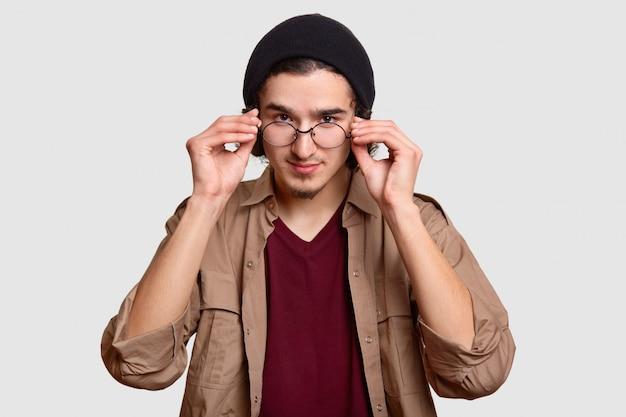 自信を持ってハンサムなひげを生やした巻き毛の男は眼鏡の縁に手を保ち、注意深く、黒い帽子とベージュのシャツに身を包んだ、白い壁にモデル。人と顔の表情のコンセプト