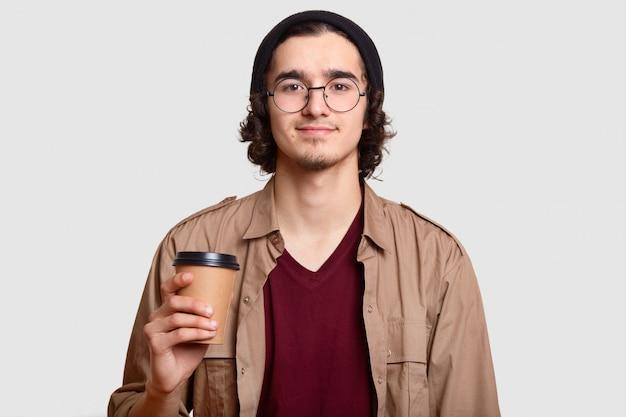 ハンサムな男の子は巻き毛を持ち、ひげは透明な丸いメガネをかけ、コーヒーを持ち歩き、休憩し、友人とコミュニケーションをとり、白い壁にモデルを描きます。人、ライフスタイル、飲み物のコンセプト