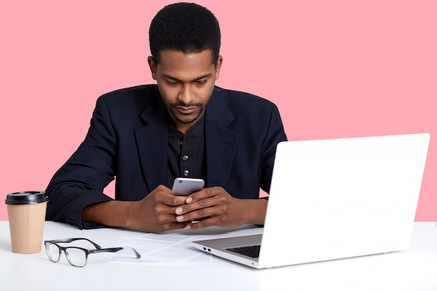 手でスマートフォンを持つ暗い肌の女性の肖像画を閉じます。ハンサムな黒人男性がラップトップでオンラインで作業し、休憩を取ることを決定し、ピンクの壁に孤立したソーシャルネットワークをチェックします。