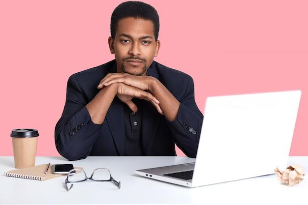 クローズアップの疲れた暗い肌の男性の肖像画はあごの下に手を保ち、正式に服を着るのに時間を必要とし、ピンクの壁に分離された彼の仕事のためにラップトップコンピューターとワイヤレスインターネットを使用します。