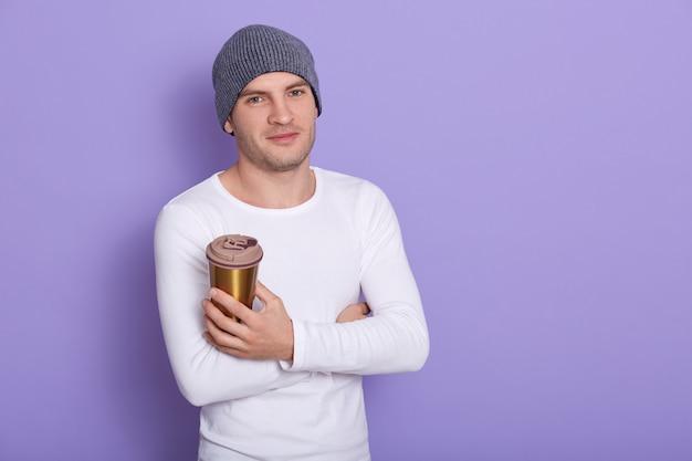 カジュアルな白い長袖シャツとグレーのキャップに身を包んだ、テイクアウトのコーヒーを手で保持している満足そうな表情でハンサムな男は、ライラックの壁に分離された温かい飲み物を楽しんでいます