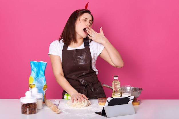 眠そうな主婦の水平ショットは小麦粉で汚れたキッチンエプロンを着てください。