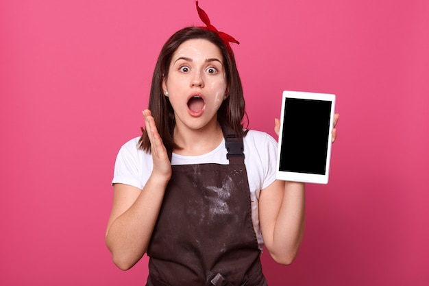 Брюнетка женский шеф-повар, повар или пекарь, держа планшет с пустой экран.