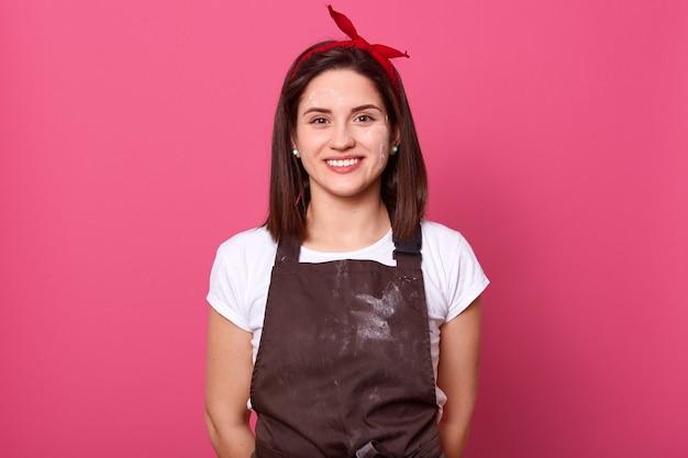 Съемка студии привлекательной женщины хлебопека нося коричневый передник