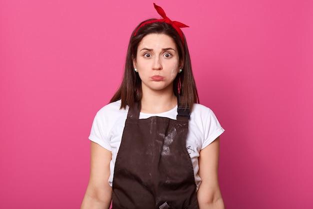 ピンクの上に孤立したポーズハード作業忙しいヨーロッパの主婦の屋内撮影