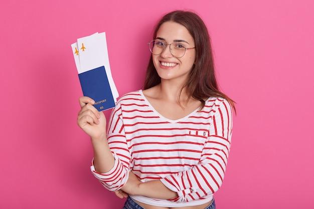 パスポートを保持している赤のストライプと白いカジュアルシャツでかなり若い女性を笑顔