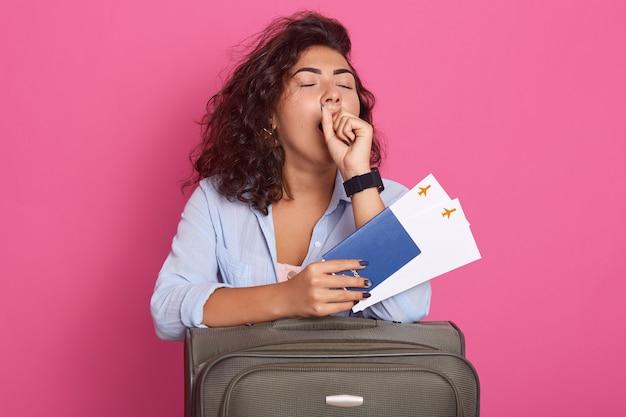 Красивая современная зевая женщина с чемоданом