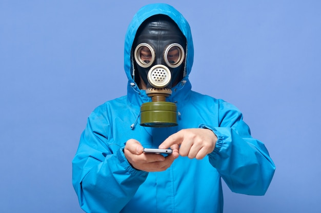 Студийный снимок неузнаваемого парня в противогазе, работающего в зоне токсинов