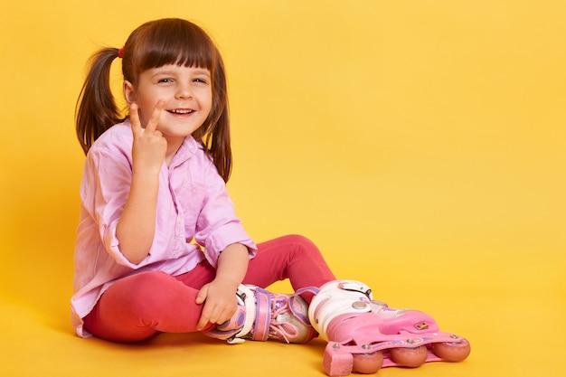 床に座って幸せな女の子の屋内撮影