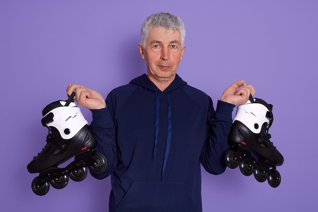 屋外でローラースケートをする準備ができている年配の男性のポートレート、クローズアップ。