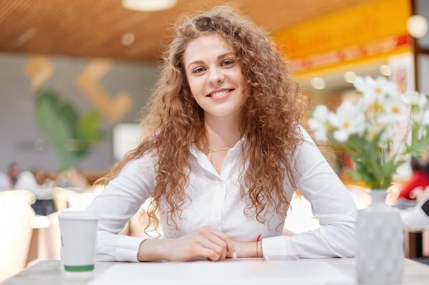 Шикарная привлекательная кудрявая молодая женщина в элегантной белой блузке