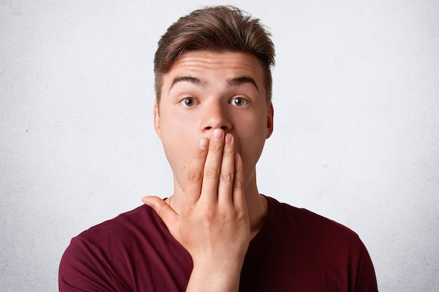 Ударная голова удивленного мужчины покрывает рот и смотрит с удивлением