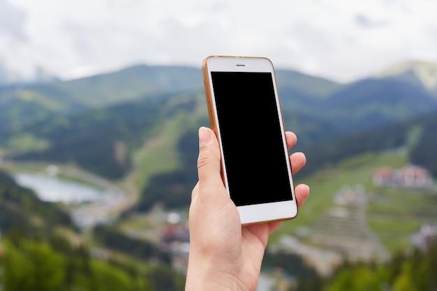 空白の画面を持つ切り替えられたスマートフォンを持っている未知の手のクローズアップ写真
