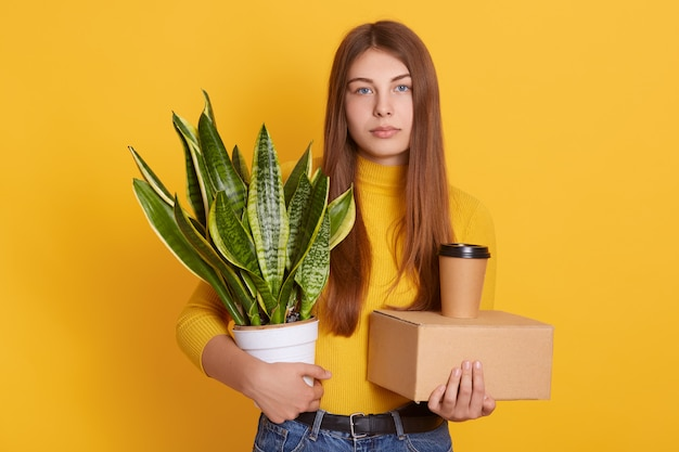 カジュアルな服装を着て長い美しい髪を持つ魅力的な女性、動揺の女性は、解任後、オフィスから彼女のものを拾い上げ、黄色の壁にポーズをとります。