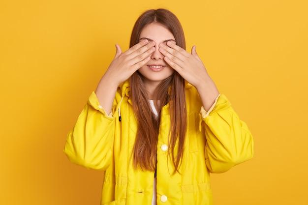 屋内でポーズをとり、手のひらでレイズを覆っている笑顔の女性、ジャケットを着ている女性、誰かから隠れている、肯定的な感情を表現している、長い黒髪の女性。