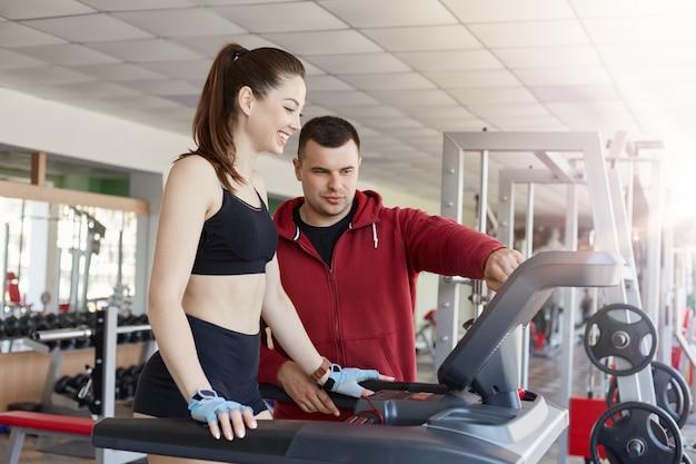 Женщина привлекательной пригонки имея физическую активность в спортзале, женщину фитнеса работая с личным тренером, даму в черной спортивной одежде бежать на беговой дорожке, девушка ведет здоровый образ жизни.