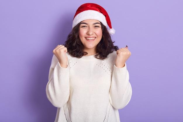 赤いサンタクロースと白いセーターを着ている美しい女性モデル