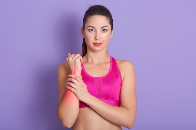 Расстроенная брюнетка молодая женщина повредила руку во время спортивной тренировки