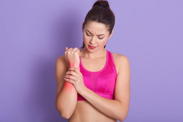 ポニーテールの深刻なブルネットの若い女性は彼女の関節炎の手をマッサージします