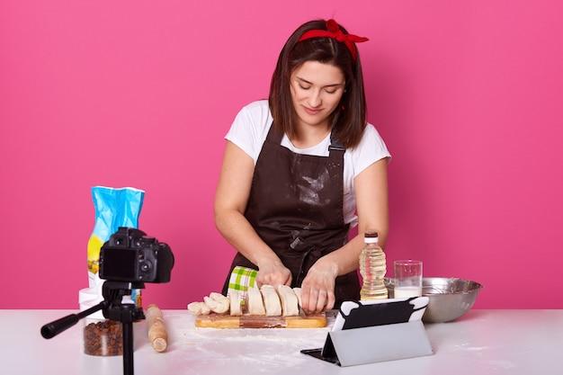 Изображение занятого умелого пекаря, стоящего над розовым
