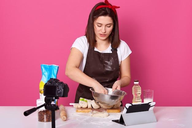 Сосредоточенная занятая талантливая домохозяйка держит миску с венчиком в одной руке