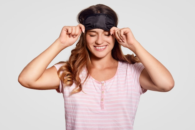 喜んで楽観的な白人女性はアイマスクを着ています