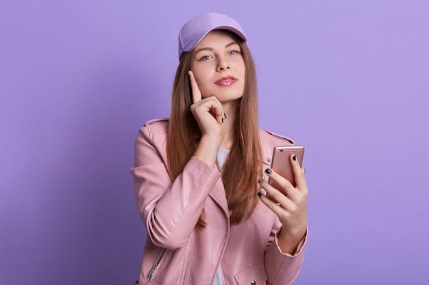 スマートフォンを手で押しながらカメラを直接見て魅力的な女性のスタジオ撮影