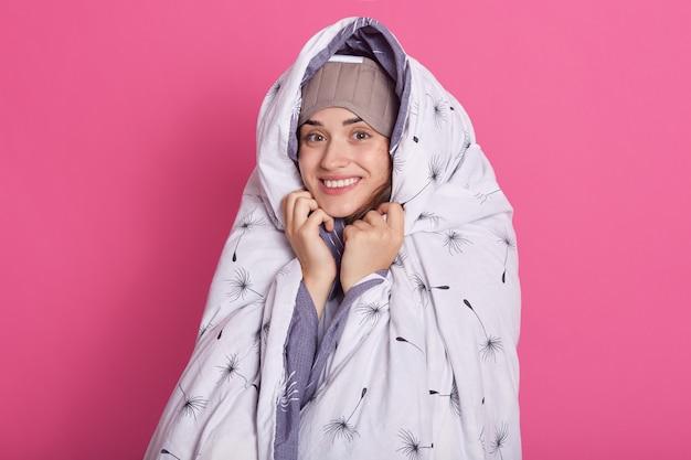 ピンクの上に孤立したかわいい魅力的な女性の地位を笑顔の屋内スタジオ撮影