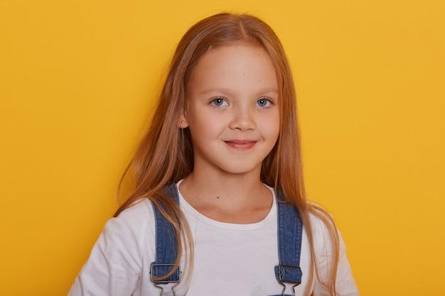 黄色で分離されたポーズをとって長いブロンドの髪を持つ美しい少女の屋内撮影
