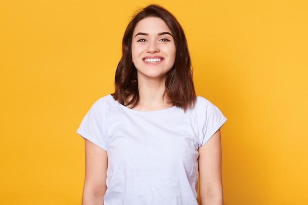 感情的な格好良い白人女性の肖像画はカメラを直接見ながら笑う