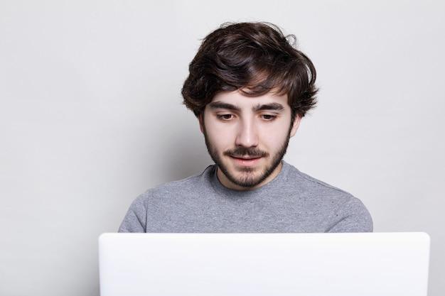 Привлекательный бородатый мужчина с изящной прической в сером свитере проводит свободное время на ноутбуке