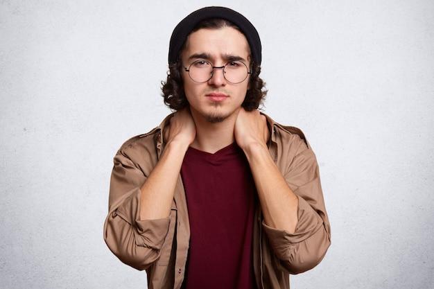 白で分離されたポーズハンサムな深刻な若い男の屋内スタジオ撮影