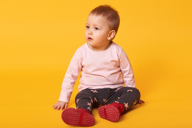 床に座っている愛らしい小さな女の赤ちゃんのスタジオ撮影