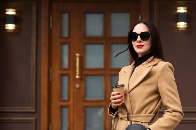 オープンエアでポーズをとってベージュのコートを着ている美しい若いスタイリッシュなブルネットの女性の屋外撮影