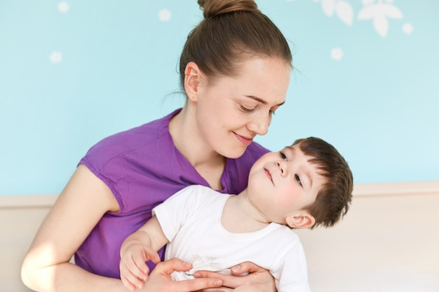 若い愛らしいヨーロッパの母は息子を抱きしめる一緒に喜びを持っています