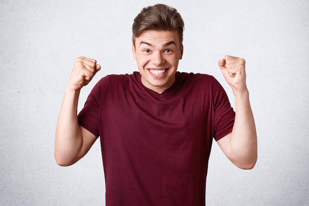 幸せなうれしそうな強い男性は拳と歯を食いしばる