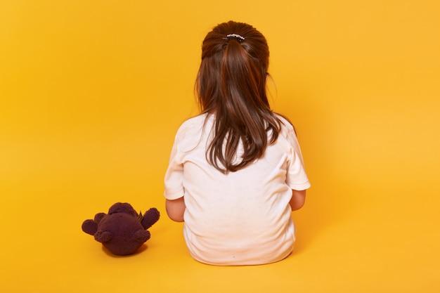 Маленькая девочка сидит в обратном направлении с коричневым мишкой