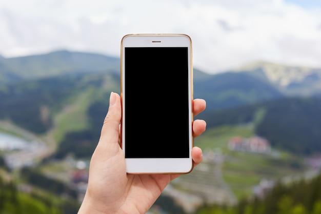 空白の黒いデスクトップ画面で白いスマートフォンを片手で見せる屋外画像