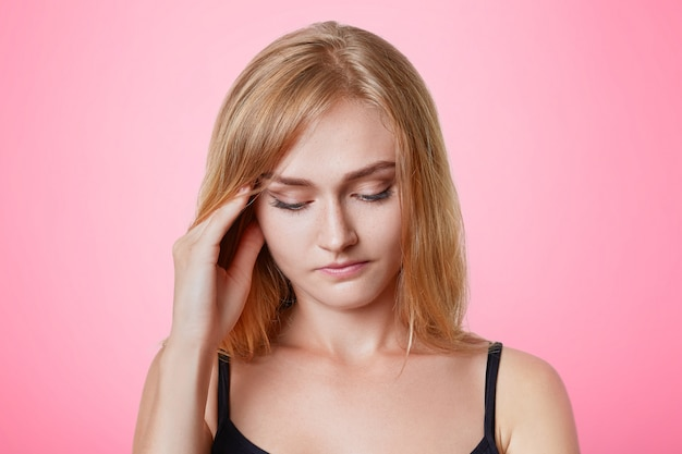 Серьезная, симпатичная молодая модель женского пола держит руку на висках, задумчиво смотрит вниз, имеет вдумчивое выражение, пытается что-то вспомнить, испытывает головную боль после долгого рабочего дня, отдыхает дома