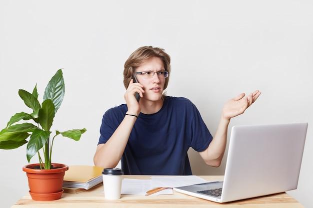 ビジネス、オフィス、テクノロジーのコンセプト。忙しい男性起業家のジェスチャー。スマートフォンでビジネスパートナーと会話し、仕事の主な問題について話し合うためにレストランでの会議を手配する