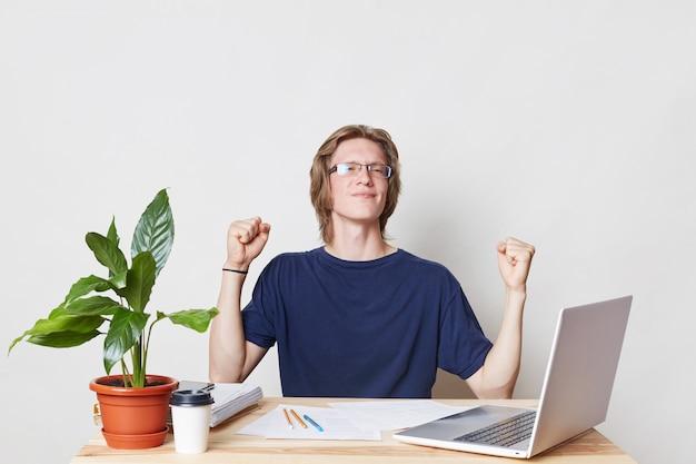 Успешный бизнесмен на рабочем месте сжимает кулаки, празднует победу и торжество, радуясь подписанию контракта с партнерами. счастливый предприниматель мужского пола радуется успехам на работе, жестикулирует от радости