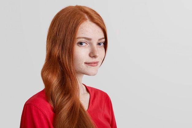 そばかすのある深刻な赤い髪の女性モデルの横向きの肖像画は、カメラに自信を持って見え、プロモーションテキストのコピースペースを白でポーズします。自信を持って生姜の女性。