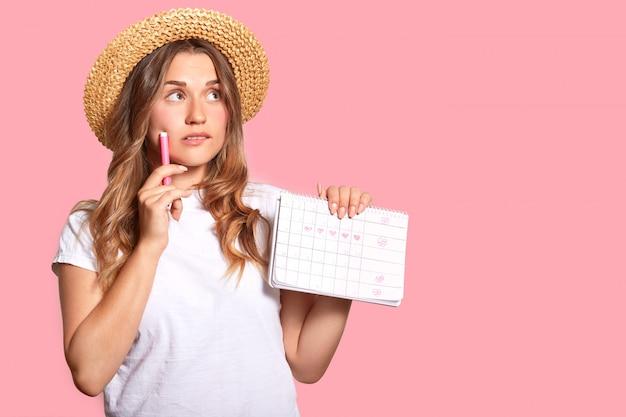 Горизонтальный снимок приятной на вид женщины с вдумчивым выражением лица, носит головной убор и повседневную футболку, держит календарь с отмеченными днями, маркер, позирует на розовой стене студии с пустым пространством