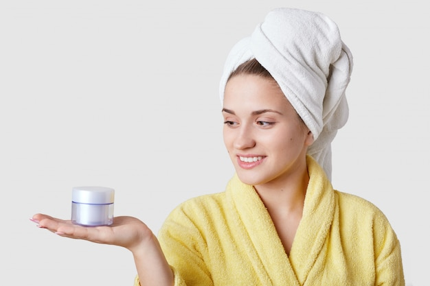 穏やかな笑顔で若い女性の水平ショット、健康な肌、バスローブ、白のモデル、顔のマスクを作るつもり