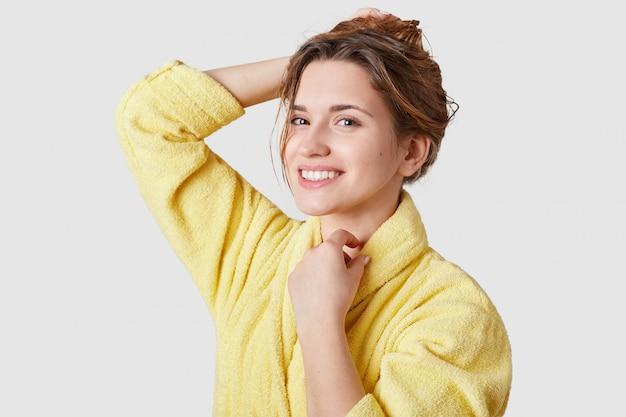 Улыбающаяся девушка без макияжа, здоровая кожа, зубастая улыбка, одетая в обычный халат, находящаяся в хорошем настроении после косметических процедур, стоит на белой стене студии. выражения лица, концепция красоты