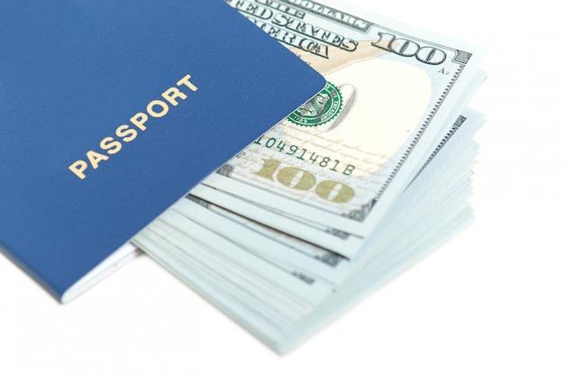 白で隔離されるパスポートのドル。紙幣と外国のパスポート。ビザなしのヨーロッパへの無料旅行。観光コンセプト。テキスト用の空き容量