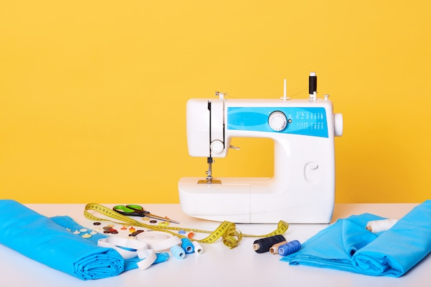 Швейное оборудование, швейная машина, метчик, ножницы, кусочки ткани, иглы, нить, изолированных на желтом. разные инструменты в швейной мастерской,