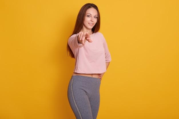 若い白人の運動女の子を指して、スタイリッシュなスポーティな服を着て、モデルのポーズが黄色に分離されました。フィットネスとスポーツのコンセプト。