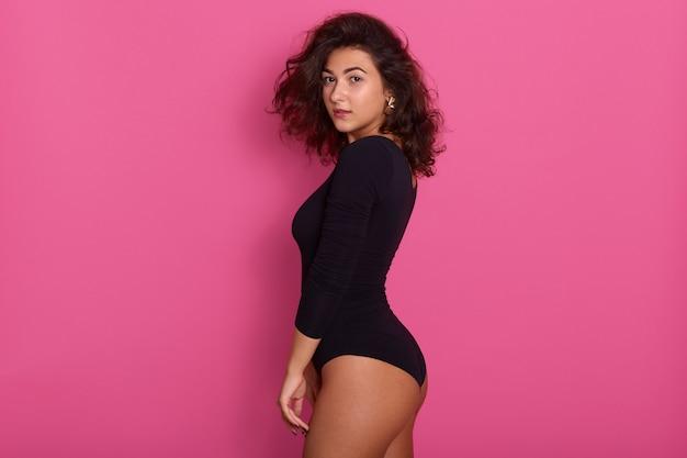 若い女性のプロファイルは、黒いウェーブのかかった髪とスタイリッシュなイヤリングを持っている魅力的な女性に孤立したピンクの魅力的な女の子にポーズをとって黒いコンビドレスをドレスします。