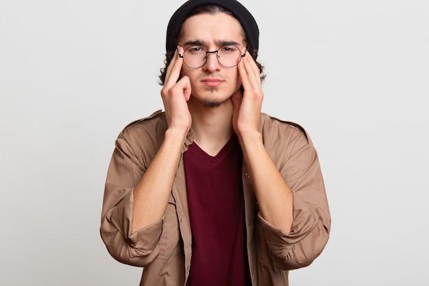 ハンサムな若者が両手でこめかみに触れ、頭痛を感じ、それを減らそうとしていると強調し、動揺しているように見えます。黒髪のスリムモデルは、黒い帽子、赤とベージュのシャツ、眼鏡を着用しています。